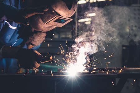 Foto für Skillful metal worker working with arc welding machine in factory while wearing safety equipment. Metalwork manufacturing and construction maintenance service by manual skill labor concept. - Lizenzfreies Bild