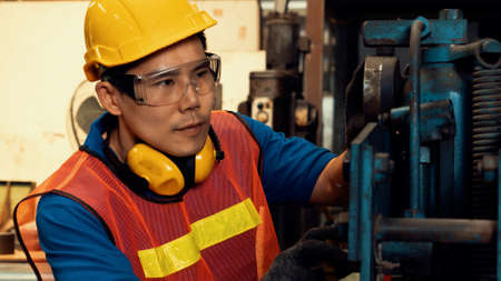 Photo pour Skillful factory worker or engineer do machine job in manufacturing workshop . Industrial people and manufacturing labor concept . - image libre de droit