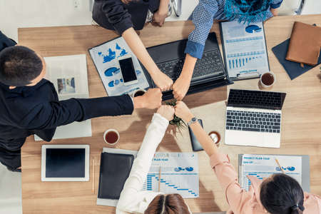 Foto de Businessmen and businesswomen joining hands in group meeting at multicultural office room showing teamwork, support and unity in business. Diversity workplace and corporate people working concept. - Imagen libre de derechos