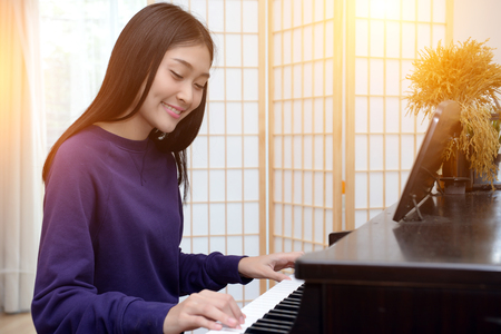 Photo pour Lovely teen playing piano in the music room. - image libre de droit