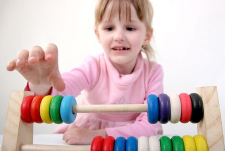 little girl make some calculation with toy coloured wooden abacus