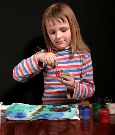 little girl dip the brush into the jar with red gouache