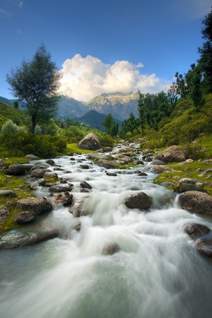 A beautiful river and Himalayan mountain background in Kashmir's Aru Valley in vertical landscape.
