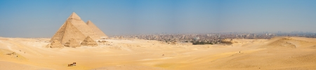 A grand panorama of all of the pyramids at Giza and the city of Cairo Egypt nearby