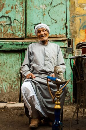 CAIRO - OCTOBER 11: A friendly old Egyptian man sits at a street cafe smoking sheesha in Islamic Cairo October 11, 2010 at Cairo, Egypt