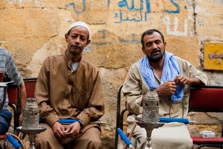 CAIRO - OCTOBER 11: A pair of Egyptian men enjoy smoking shisha at a traditional streetside ahwa (cafe) in Islamic Cairo October 11, 2010 at Cairo, Egypt