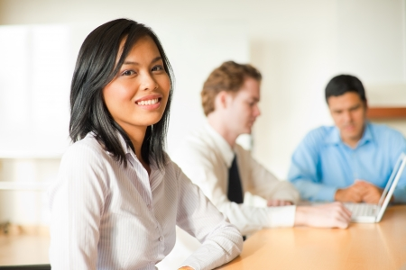 An attractive Asian businesswoman looks at the camera during a meeting with a diverse group of business people including a latino and caucasian male.