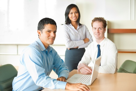 A latino businessman leads a diverse team of business people including an attractive Asian woman and caucasian male.