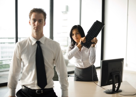 A female office employee swings a keyboard to mock hit her male boss over the head.