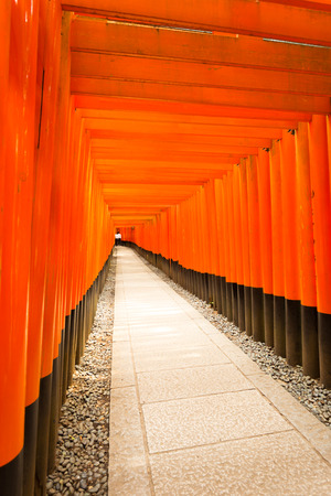 Unidentified students inside the far end of vanishing point repeating red torii gates and stone footpath at Fushimi Inari Taisha Shrine in Kyoto, Japan. Vertical copy space