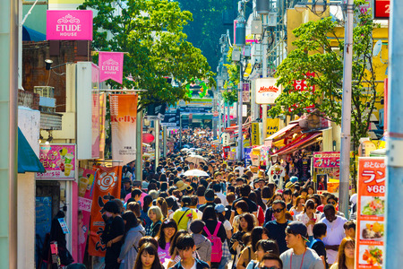 Tokyo, Japan - June 24, 2016: Many young people walking down crowded and bustling shopping street in consumerism mecca lined with stores on busy Takeshita Dori