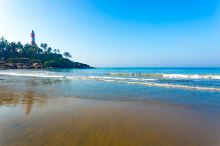 Photo pour Light house standing above the rocky outcrop above the ocean waves at Kovalam Beach in Kerala, India. Horizontal - image libre de droit