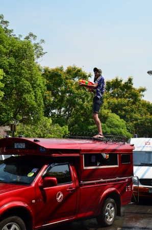 CHIANG MAI, THAILAND - APRIL 13 : Tourist stand on bus roof for celebrating Songkran (Thai new year / water festival) on 13 April 2013 in Chiang Mai, Thailand