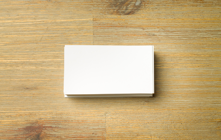 Stack of white aligned business cards on a brown wooden table.. A copyspace for your businesscard. Small rectangle shaped carton.