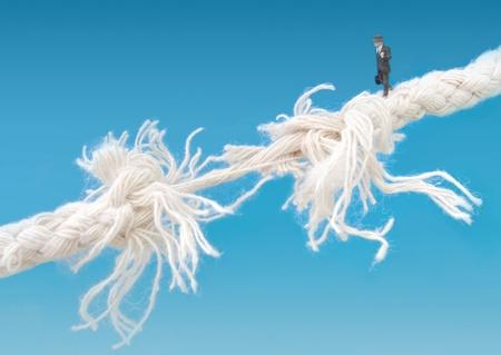 Businessman on breaking tightrope