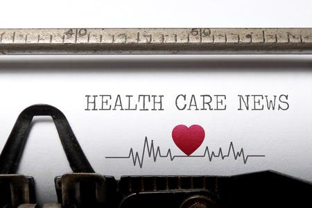Foto de Health care news printed on an old typewriter with heart beat pulse sketch - Imagen libre de derechos