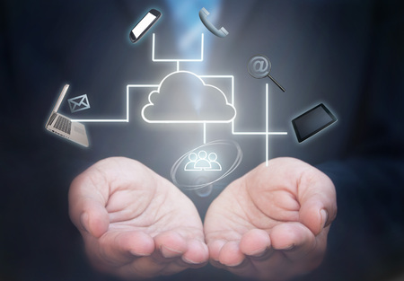 Foto de Business man holding a network of computer gadgets and social media icons stemming from a cloud icon - Imagen libre de derechos