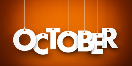 October word suspended by ropes on brown background