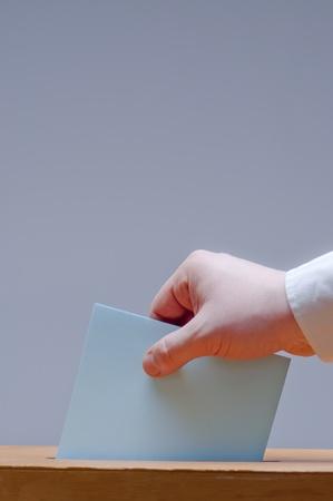 voter puts ballot in a ballot box