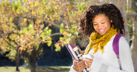 Photo pour Pretty African American Black female student texting or using mobile phone. Room for copy or text over Fall trees in background . - image libre de droit