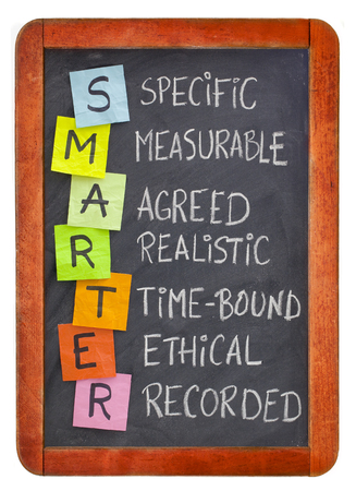 Photo for SMARTER (specific, measurable, agreed, realistic, time-bound, ethical, recorded) - acronym for goal setting methodology, white chalk handwriting, colorful sticky notes on isolated blackboard - Royalty Free Image