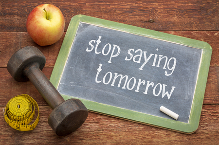 Photo pour stop saying tomorrow  - white chalk text on a slate blackboard against weathered red painted barn wood with a dumbbell, apple and tape measure - image libre de droit