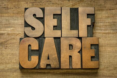 Photo for self care word abstract in vintage letterpress wood type on grunge handmade paper - mental, emotional, and physical health concept - Royalty Free Image