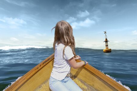 A girl in a wooden boat swims towards a buoy