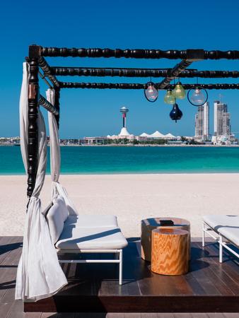JAN 31, 2015 Abu Dhabu, UAE - Modern Beach Gazebo white curtain with white seat and wooden stool table. Blue sea under clear summer sky at Corniche beach with Marina island in background