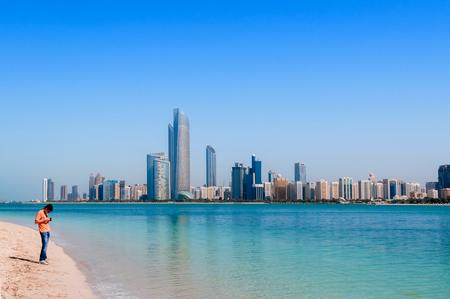 FEB 2, 2015 Abu Dhabi, UAE - European tourists at white sand beach blue sea with Abu Dhabi skyline and cityscape view from marina island