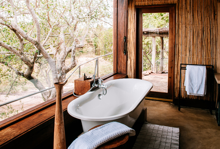 Photo for JUN 20, 2011 Tanzania - Open air bathroom with luxury bathtub with forest view - African Boho safari camp interior decoration with wooden bamboo wall. - Royalty Free Image