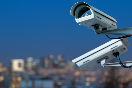 Photo pour Focus on security CCTV camera monitoring system with panoramic view of a city on blurry background - image libre de droit