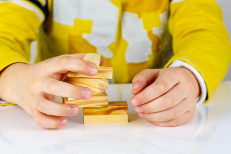 Child hands playing with wooden blocks the unstable tower. Building collapse games
