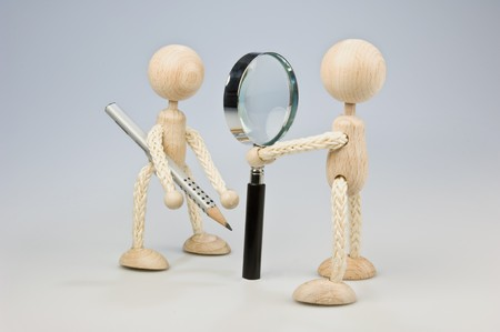 Two wooden dolls looking to each other trough a magnifier