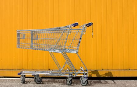 Two empty shopping carts in front of a yellow wall