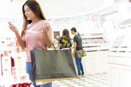 Young female holding two bag, mockup blank screen paper shopping bag with clipping path, Empty space on shopping bag for design insert graphic.