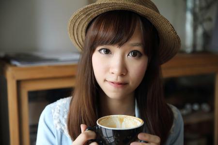 Photo pour Asian girl indoor drinking coffee - image libre de droit