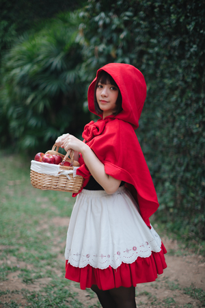 Foto per Portrait young woman with  Red  Hood costume in green tree park - Immagine Royalty Free