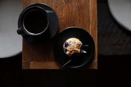 Photo pour Coffee cup with muffin on wood table in local coffee shop - image libre de droit