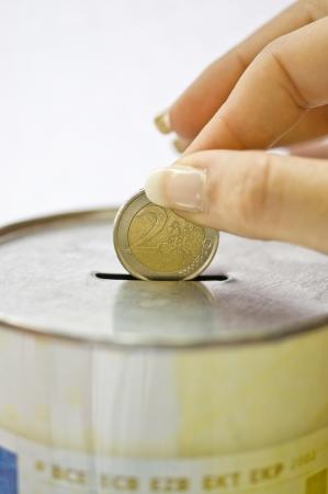 Human hand put some money in moneybox