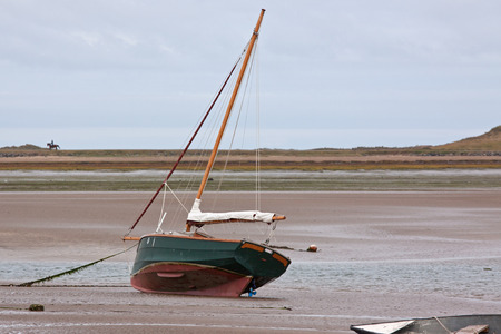 Beached sail boat on the Devon coast UK