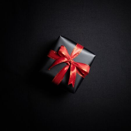 Photo for Top view of black gift box with red ribbons isolated on black background. Shopping concept boxing day and black Friday sale composition. - Royalty Free Image