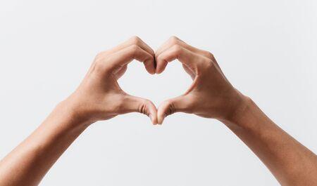 Photo pour Man hands making a heart shape on a white isolated background - image libre de droit