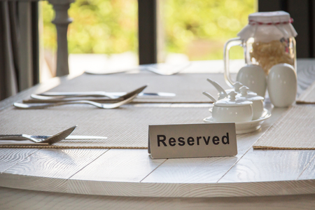 Foto de Reserved sign on a table in restaurant by the window. - Imagen libre de derechos