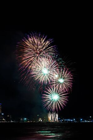 Photo pour Fireworks over sea with city night on background. Festive colorful fireworks celebration in night sky. - image libre de droit