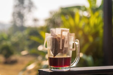 Photo pour Drip brewing; clear glass of coffee mug and paper dripping bag with ground coffee in warm sunlight at garden tree on background. - image libre de droit