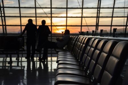 Photo pour Silhouette of a airport at sunset. Seats for waiting flights at the airport. Concept of business and travel in modern lounges. - image libre de droit