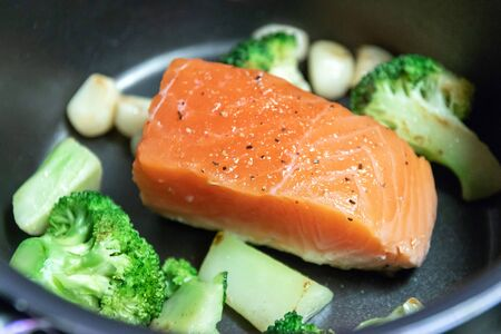 Photo pour Cooking salmon steak on pan with broccoli and garlic. Grill salmon fillet. - image libre de droit