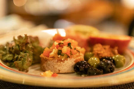 Photo for Classic Italian appetizer dish; bruschetta with heirloom tomatoes and olives in warm light romance restaurant dinner. - Royalty Free Image