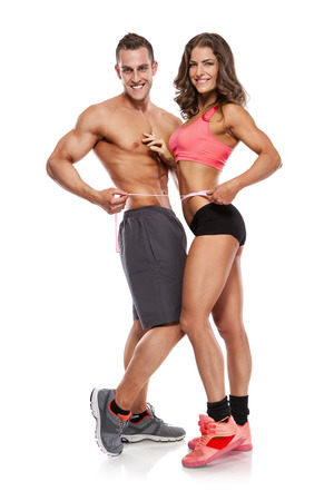 Photo for beautiful young sporty couple with a measuring tape isolated over white background - Royalty Free Image